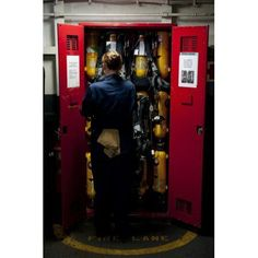 Fireman stows a self-contained breathing apparatus in a locker Canvas Art - Stocktrek Images (23 x 35)