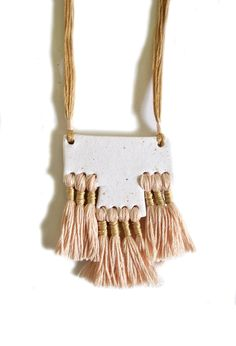 CIENEGA NECKLACE BY OBJECT DESIGNER, WILD COLUMBINE.  FORMING USING AN USUAL COMBINATION OF WHITE CLAY AND SOFT BLUSH AND METALLIC GOLD YARN FIBRES GIVES THIS TASSEL NECK PIECE A CONTEMPORARY EDGE AND MODERNISED FEEL.   STYLE  WEAR WITH A SILK NUDE CAMI, OVERSIZED CHAMBRAY SHIRT AND SUPER SOFT TAN LEATHER SHOPPER BAG FOR A STYLISH, RELAXED LOOK.   SIZE  HANGING LENGTH 43CM. CLAY PENDANT WIDTH 6.5CM, LENGTH 5CM.  #UnusualNecklace #RopeNecklace #RopeJewellery #WovenNecklace