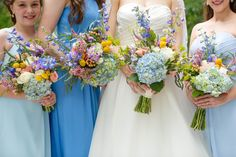 The perfect mix-match blue bridesmaids dressed and wild flower bouquets for any wedding. Bouquets with hydrangeas, pink and white roses,  peonies, and other wildflowers. Katie & Alec Photography, The Barn at Shady Lane wedding photographers in Birmingham, Alabama.The Barn at Shady Lane wedding photographers