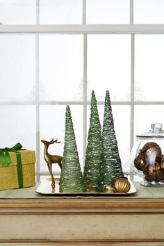 Create these tall, delicate trees by wrapping the top of a foam cone with cardstock to create a true point (the tops are flat), then cover the cone in clear plastic wrap. Knot a piece of green embroidery floss around the top, then wrap it around the cone in a crisscross pattern.(To make shorter trees, stop wrapping before you get to the bottom of the cone.) Apply 2 coats of Mod Podge Stiffy (available at craft stores) to the floss; once dry and hardened, remove the plastic wrap an...