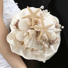 For beach-themed and destination weddings, this seashell bouquet makes a great accessory for the bride to hold. The clear acrylic handle holds a bouquet made of an ivory satin ruffle and a collection Beach Wedding Bouquets, Beach Wedding Colors, Beach Wedding Reception, Wedding Rehearsal, Floral Wedding, Wedding Dresses, Seashell Bouquet, Lillian Rose, Maroon Wedding