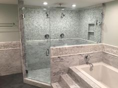 Emerald City Tile and Stone, LLC; Shower in Carrara marble 6 x 12 set in running bond pattern transitioned by carrara marble chair rail to 1 x 2 carrara marble set in herringbone pattern. Grouted in High White urethane grout by Quartzlock. Moen trim in chrome. Glass by AAA Kartac.