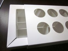 Box frame tray with insert and sleeve with 8 die-cut circles and plastic film to protect product #packaging