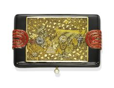 AN ART DECO GOLD AND ENAMEL VANITY CASE. The rectangular black enamel case, set with a panel depicting japanese gold and silver flower motifs, enhanced by two red enamel circular details and a pearl pushpiece, opening to reveal a fitted mirror, covered compartment and a lipstick holder, circa 1925, 8.4 cm long, no. 3279, with French assay mark and English import hallmarks for gold