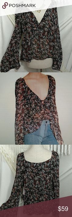 """NWT!  Free People Uptown Bell Sleeve Blouse A low-cut surplice neckline adds boho style to a  breezy bell-sleeve blouse.  Feminine botanical print.  Elastic gathering at shoulders.  Flowy ruffle trim details.  Length:. Approx 23""""  100% rayon (machine wash cold).  Color:. Black w/orange, light grey, and cream floral print (see picture #7) Free People Tops Blouses"""