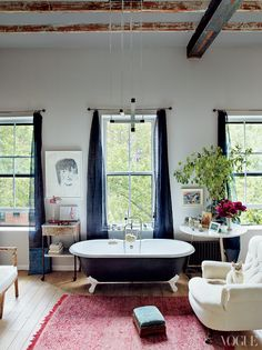 A vintage tub anchors the master bathroom-drawn to the easy linen drapes