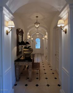 classic black and white tiled floor, warm lighting, squared furniture as juxtaposition to arched ceiling
