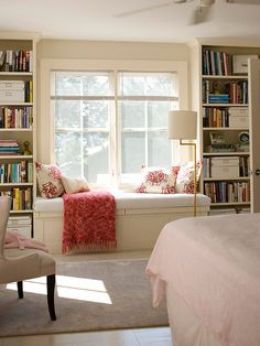 bookshelves on either side of a twin bed under a window for the guest room/office