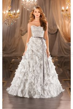 A-line designer wedding gown in Parisian Silk Chiffon features encrusted Swarovski crystals, diamantes and freshwater pearls on the scalloped sweetheart bodice to the natural waist and a dramatic textural skirt.  Valencia satin ribbon sash included. Zipper back closure with fabric buttons.
