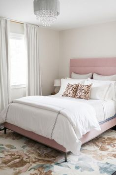 Lovely transitional bedroom is lit by a gray sheer drum chandelier hung over a brown and gray floral rug in front of a pink velvet upholstered bed dressed in white and gray bedding accented with matching shams layered behind pink and brown animal print pillows.
