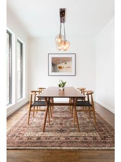Love this dining space by Lulu and Georgia! Shop the look! #LANDGATHOME  modern dining // dining room ideas // globe lighting // traditional rug // minimalist dining room // modern decor