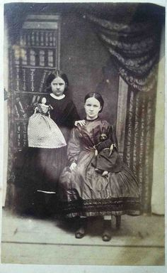 Originally pinned as a post-mortem, in spite of some peculiarities, the seated girl still does not appear to be deceased. It was customary during this era for a person in mourning to turn their face away from the camera, and the doll in her lap has been turned so that its face doesn't show. Would certainly love to know the story behind this photo.