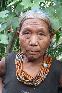 India | Konyak woman.  The red ear adornments come from a local plant.   Upper Konyak village, Nagaland |  ©Rita Willaert