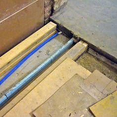 3/15 Koska rakennuksen uudeksi lämmitysmuodoksi oli valittu kaukolämpö vedettiin myös kylpyhuoneen uuteen laattaan vesikiertoinen lattialämmitys. Laatta tehtiin tämän takia kaksiosaiseksi ja betonilaattojen väliin laitettiin kevyt eristekerros. Näin estettiin lämmön valuminen harakoille. Kuvassa näkyy myös miten kevyellä eristekaistalla uusi betonivalu laakeroitiin irti alapohjan puurakenteista. Näin materiaalien erilainen eläminen kosteuden ja lämpötilavaihteluiden mukaan ei muodostu…