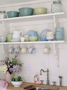 open shelves, decorative brackets, homeowner stages dishes on the wall behind her day to day plates so that when they are in use theres still something pretty to look at