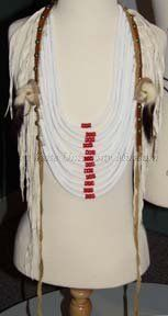 """1900-1980  """"Men's breast plate, Plateau Indian, Probably Crow or Nez-Percé,  White glass beaded wrapped rope, red """"pony"""" beads, abalone shells, ermine fur tails, brass studs, commercially tanned smoked and unsmoked (white) leather.  Probably used as dance regalia."""" Material   Deerskin/Beads"""