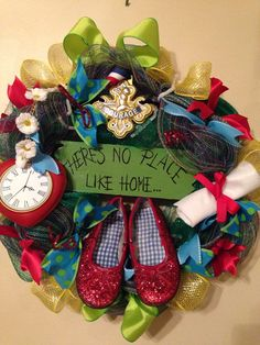 Approximately 20 emerald green deco mesh wreath with coordinating ribbon and wizard of Oz inspired decorations. In the center sits a pair of red glittered shoes and and sign saying theres no place like home. Ornamentation may vary slightly due to availability.