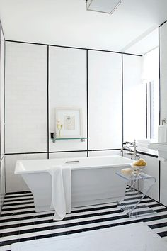 """ANN SACKS 3"""" x 6"""" Nero Marquina marble field and 9/16"""" x 8"""" box liner molding in honed finish with White Thassos 3"""" x 6"""" field in honed finish and KOHLER reve freestanding tub, Clearflo slotted bath drain, Finial traditional bath faucet, and Pinstripe glass shelf (location: Veranda show home in New York; designer: S. Russell Groves)"""