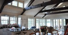 I adore this look! Dark beams, white-washed walls/ceiling with clean white beadboard. TONS of windows!