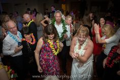A bride and groom dance with their friends and family at their wedding reception, held in the historic Riverside Hotel in Ft. Lauderdale, Florida. Following a quiet, at-home ceremony, the party took on a beach luau theme, with flower leis for the guests and newlyweds, flip flop sandal favors, and a ukelele solo for the first dance. The John Parker Band joined the fun, adding music and laughter to the couple's big day! http://www.jpband.com/weddings/