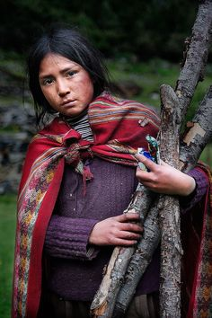Girl in Peru collecting firewood for her adobe home