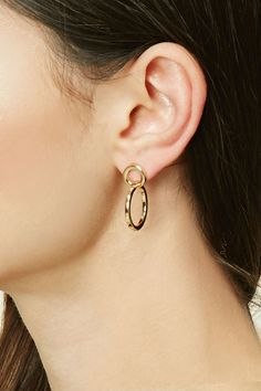 A pair of high-polish drop earrings featuring circle cutouts and a post back closure.