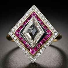 Art Deco Style Diamond and Ruby Ring. A unique and stunning jewel, crafted in homage to enduring Art Deco style and featuring an unusual diamond-shape (as in playing cards or baseball) step-cut diamond, framed concentrically with gorgeous calibre French-cut rubies and glittering full-cut diamonds. For added dramatic effect, the diamond is delicately outlined in black enamel.