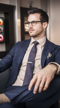 Notch lapel navy suit with light salmon shirt Tie bar and pocket square