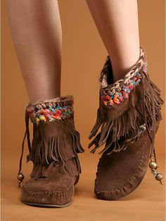 Fringe Moccasin Boot | Suede fringe moccasin ankle boot with knotted fabric and braided yarn at the top. Drawstring suede tie with embellished details. Boot is lined with leather. Rubber sole. Free People By Jeffery Campbell.