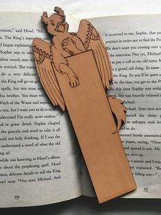 This leather griffin bookmark features the mythical beast gazing at a pocket watch. While I am no griffin expert this one seems to be fixated on keeping time… who else would you trust to help you keep track of time more? (Well aside from a watch.)  Anyway this whimsical bookmark design is unique to Raven King Crafts and features the griffon at the top of the bookmark with its tail protruding from the side. This design allows you to place the griffon so he peeks over the pages at you. Since…