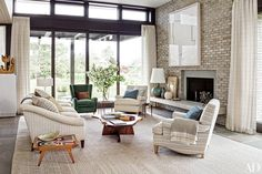 At a Bridgehampton, New York, house devised by architecture firm Deborah Berke Partners, with interior designer Thomas O'Brien of Aero Studios, a large Richard Prince artwork surveys the living room, which includes a pair of club chairs (clad in a Great Plains fabric) and a Jonas sofa facing a George Nakashima cocktail table.