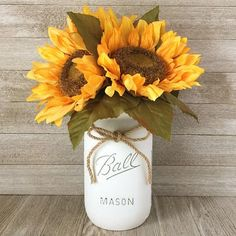 A jar of sunshine, this lovely silk floral arrangement oozes southern charm, set in a hand painted and distressed Ball mason jar with a tight and moun. Sunflower Arrangements, Silk Floral Arrangements, Artificial Flower Arrangements, Artificial Flowers, Sunflower Wedding Centerpieces, Mason Jar Flower Arrangements, Sunflower Decorations, Centerpiece Flowers, Wedding Ideas With Sunflowers