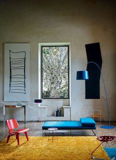 In this Foscarini-designed space, a Twiggy floor lamp by Marc Sadler hangs over a daybed upholstered in a bright blue shade. A scruffy rug and an Eames Molded Plywood Lounge Chair in cherry red complete the primary color aesthetic. Twiggy, Living Room Inspiration, Interior Design Inspiration, Interior Exterior, Interior Architecture, Design Furniture, Modern Furniture, Living Divani, Led Floor Lamp