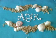 Detail on beach engagement cake with chocolate seashells.