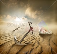 stock photo of boat anchor and dry tree in the desert