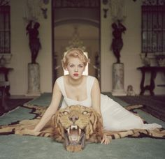 'Beauty & the Beast' by Slim Aarons - Lady Daphne Cameron on a tiger skin rug in the trophy room at socialite Laddie Sanford's home, Palm Beach Florida (c1959)