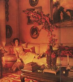 The Duchess of Windsor at home. A cream, red and gold needlepoint rug with a red leaf border anchors the cream silk sofa and Chinoiserie coffee table stacked with books. Note the exposed wood floor between the sofa and the needlepoint rug.