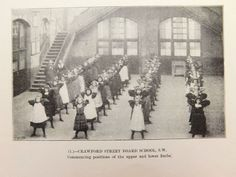 A vintage black-and-white photograph showing an everyday school class from around 1905 It shows a PE lesson also known as physical instruction