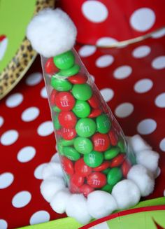 Santa hats provided a sweet favor. To make these, fill a disposable icing bag with a scoop of red and green candies. Secure the bottom with a twist tie, and cut off the excess bag. Hot glue small pom-poms around the base of the hat and a larger one to the top.