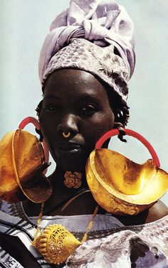 "Africa | Scanned image from the National Geographic publication August 1975 ~ article entitled 'The Niger: River of Sorrow.  River of Hope'.  Text and photos by Georg Gerster.  Caption to this photos ""Earmarks of wealth among the Fulanis, giant gold ornaments festoon a woman at Dialloube; a head strap often helps support the heavy earrings.  As the family's fortune increase, more gold may be hammered onto the jewelry"""