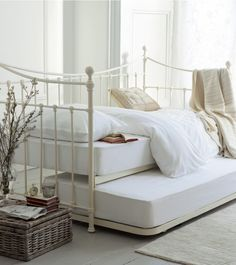Hastings Day Bed - Ivory Victorian style day bed with three railed sides, a sweeping top rail, shell design detail, hand-pouredcastings and sprung slats; complete with basic open coil mattresses; trundle legs raise mattress to same height as day bed - Metal beds