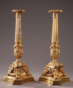 Paire de flambeaux en bronze doré. Chaque flambeau repose sur une base trilobée à pans incurvés. La base est surmontée par trois chimères supportant le fût décoré de feuillages et...