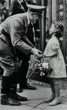 Hitler accepts a basket of flowers from a young German girl. In an alternate (and far less horrific) reality, this picture could be a heartwarming scene of a benevolent leader and his young subject. Germany Ww2, Genuine Smile, German Girls, The Third Reich, Second World, Historical Photos, World War Ii, Old Photos, Wwii