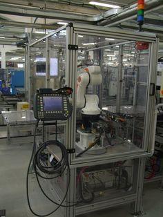 Banco robotizzato con Kuka KR6 per montaggio e controllo con telecamera componenti.