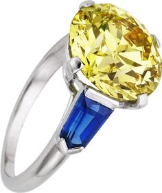 Art Deco Fancy Intense Yellow Diamond, Sapphire, Platinum Ring, Cartier  The ring features a European-cut fancy intense yellow diamond measuring 11.15 - 11.35 x 7.02 mm and weighing 5.50 carats, enhanced by shield-cut sapphires weighing a total of 1.20 carats, set in platinum, marked Cartier
