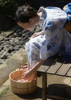Japanese woman washes feet, possibly prior to a tea ceremony. Possibly because her gets are killing her.