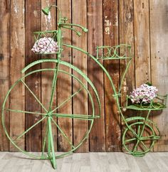 A large green metal penny farthing bicycle plant stand that is perfect for the patio or to brighten up a dull wall or fenced area in your garden