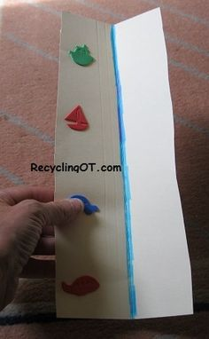 Child practices placing thumb on each sticker moving from bottom to top, then does it while cutting on the line to learn how to stabilize paper near the area being cut. RecyclingOT.com