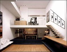 """A huge skylight (not shown) caps the three-story-high living room. Current owner Sachs has put """"Le Cri,"""" his series of photographs of Claudia Schiffer's lips, by the staircase. The door on the right on the mezzanine leads to the master bedroom. The hallway downstairs leads to the front door. The Lucite dining table, designed by Rudolph, is gone, replaced by one in white oak.   (Photo credit: Nikolas Koenig)"""