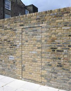 """Brick wall door - """"This not-so-secret door is one way to deal with a lot that borders directly on a public sidewalk – while not concealed per se, it does blend beautifully into the background, while the rest of the brick wall provides privacy."""""""